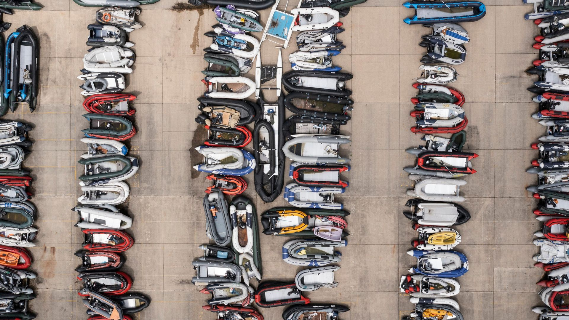 Inflatable dinghies used by migrants to cross the channel from France are stored in a compound in Dover, England - Credit: Getty Images