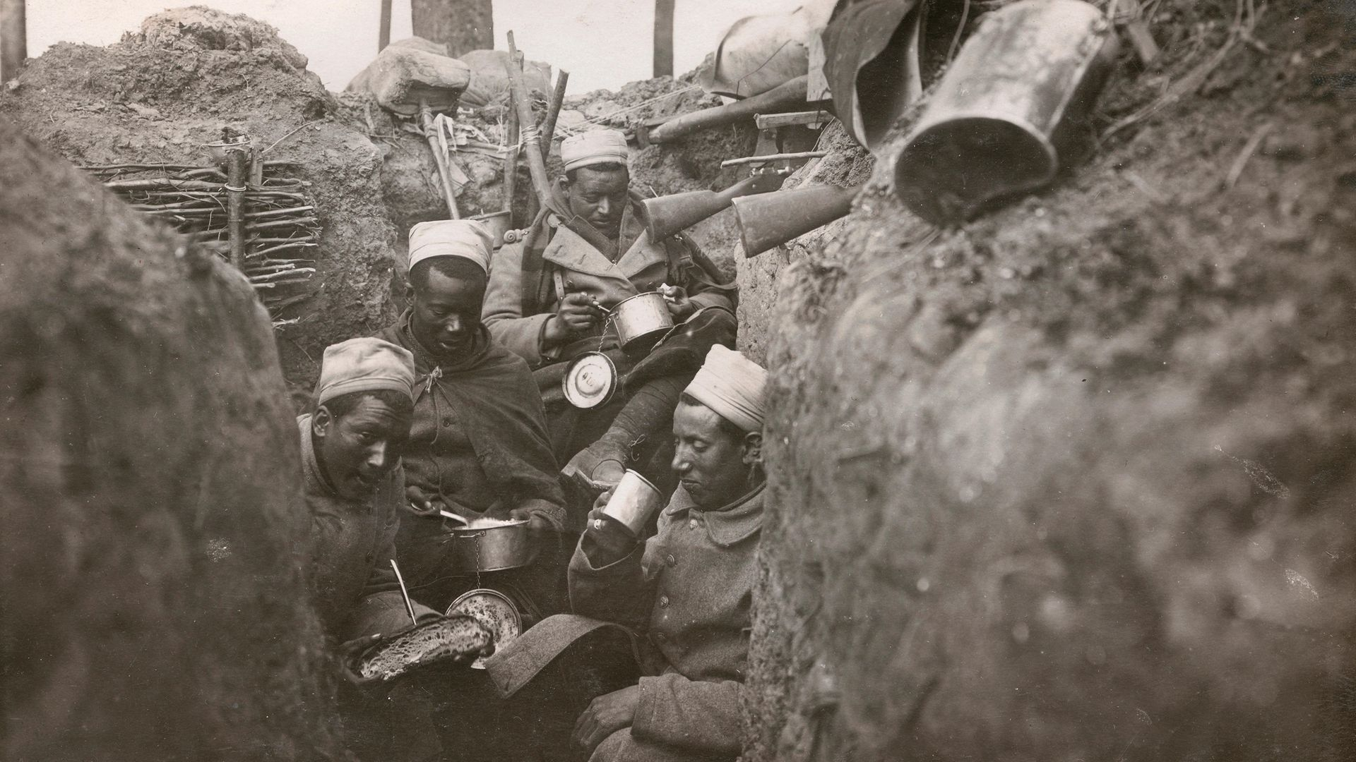 Senegalese infantrymen in the French army eat in their trench, in a photograph from 1915 - Credit: Corbis via Getty Images