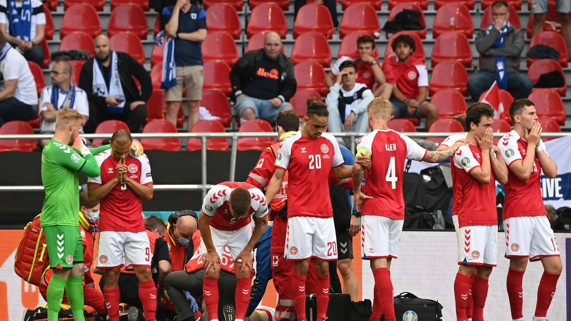 Shocked Denmark players gather around teammate Christian Eriksen after his collapse in the Euro 2020 match against Finland - Credit: Photo by JONATHAN NACKSTRAND/AFP via Getty Images