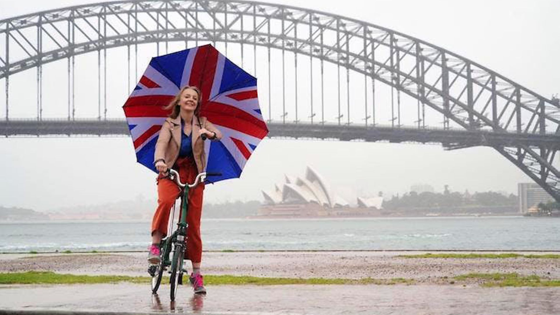 Liz Truss poses with a union flag umbrella as she takes visits Syndey to promote post-Brexit Britain - Credit: Twitter