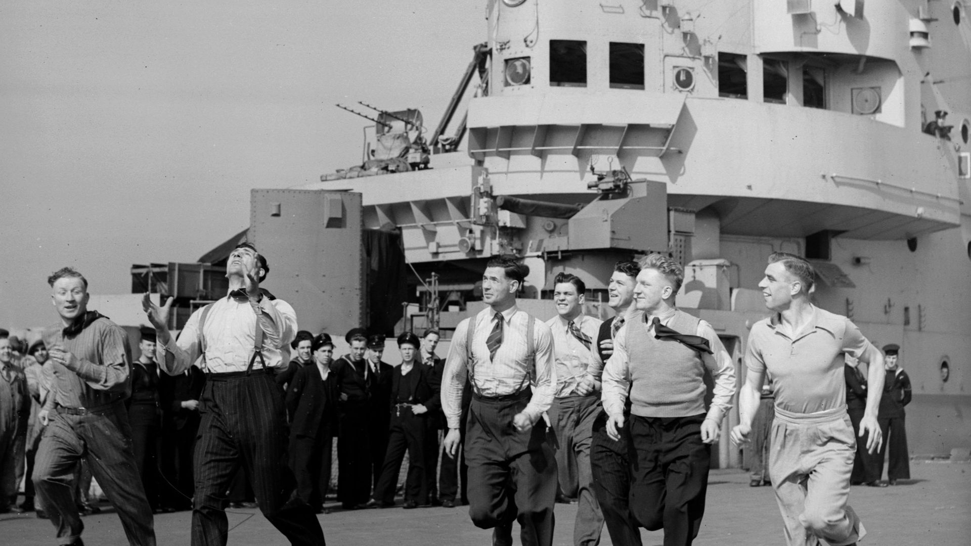 The British Lions rugby league team toss a ball around on the deck of the aircraft carrier HMS Indomitable, bound for Australia - Credit: Getty Images