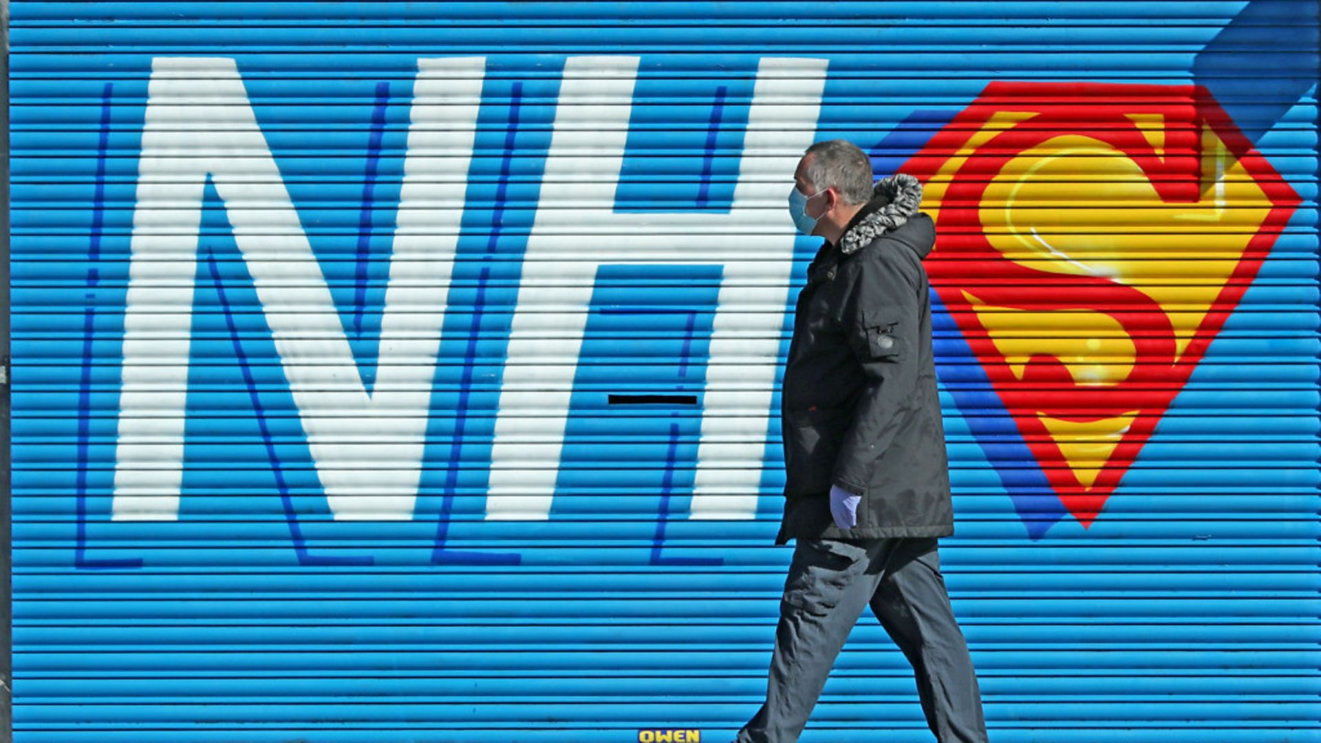 A man walks past a sign created in support of the NHS during the pandemic - Credit: Peter Byrne/PA