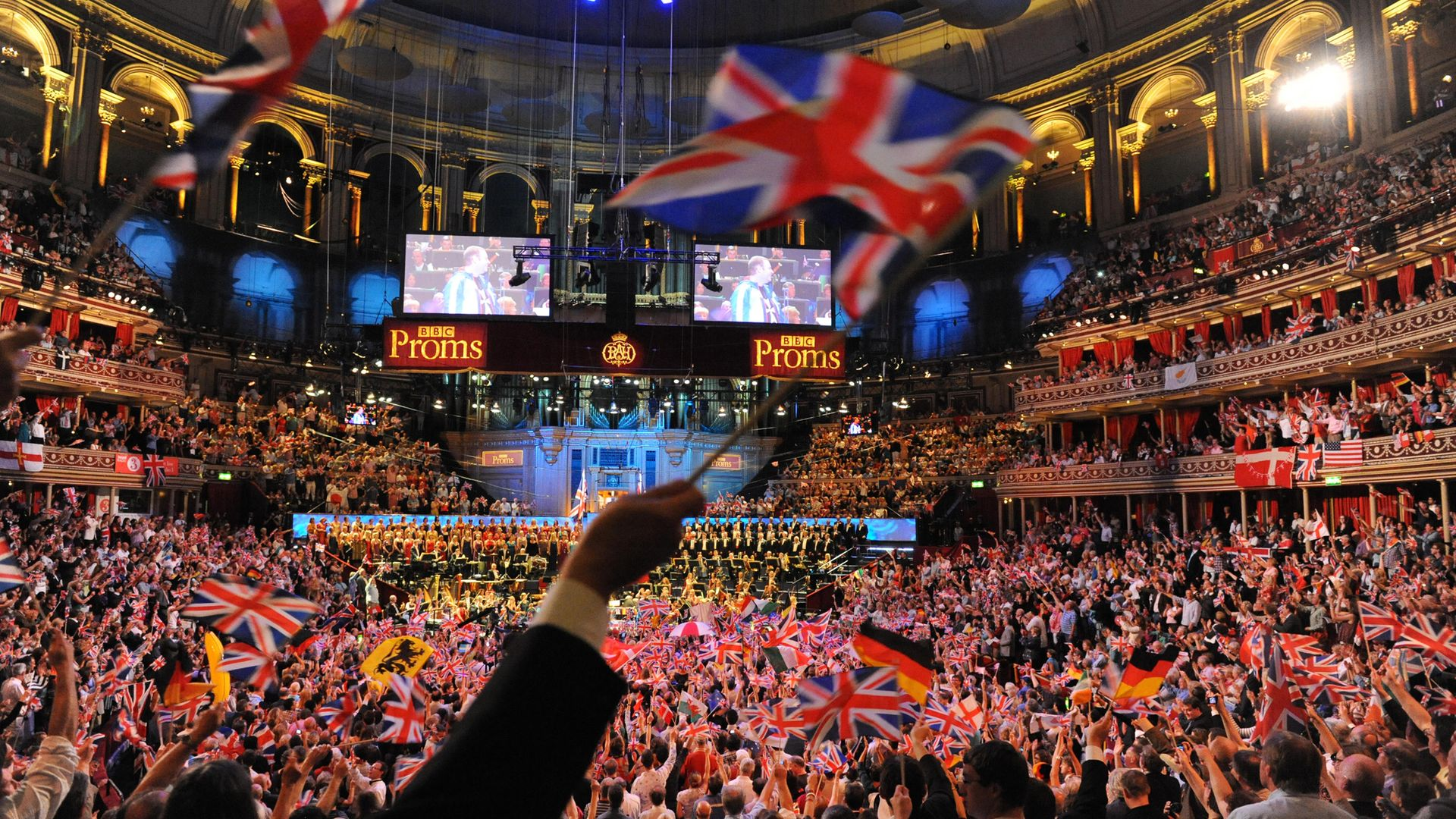 Union flags (and those of other nations) are waved during the climax of Last Night of the Proms - Credit: Redferns via Getty Images