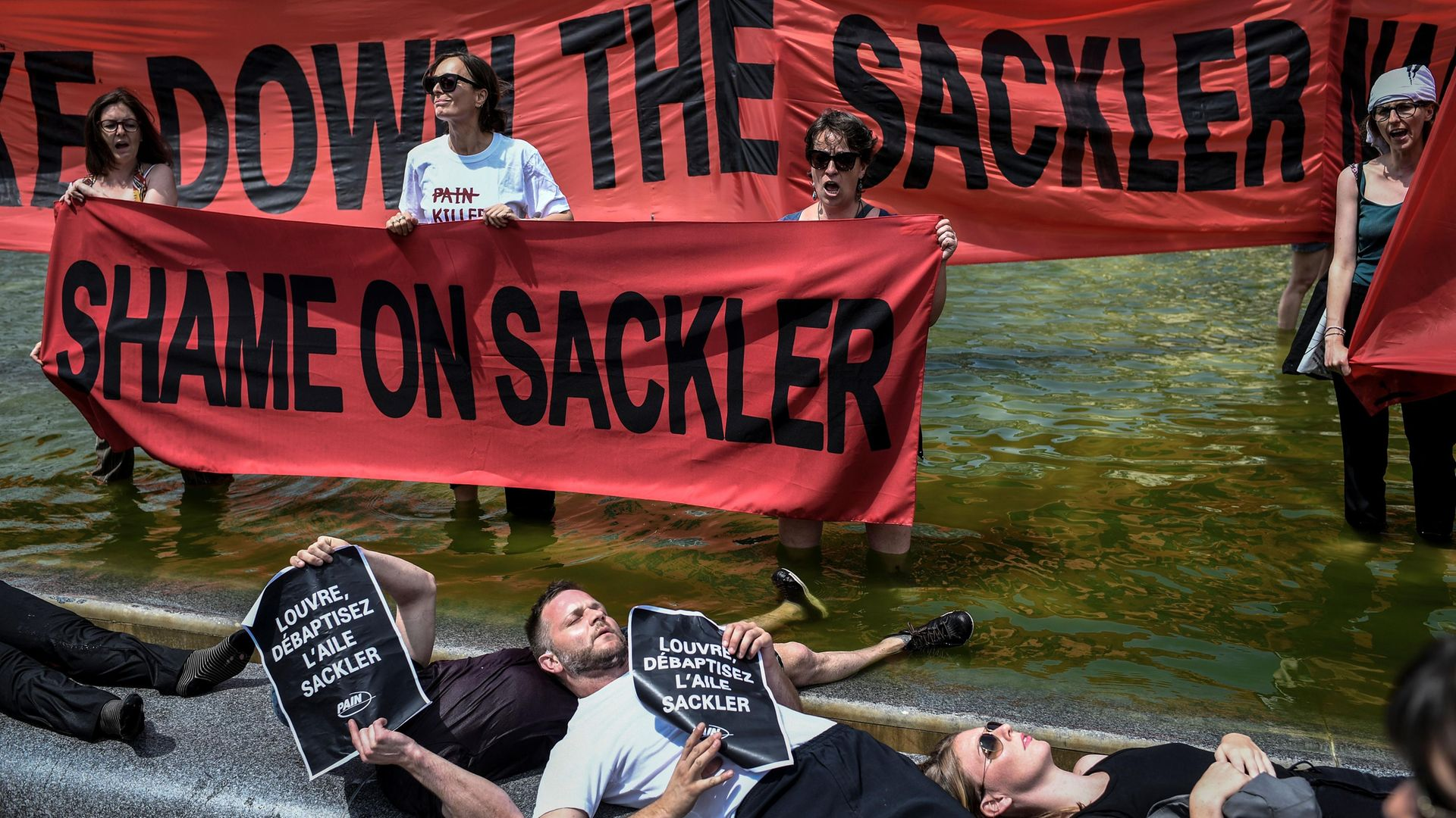 Activists protest against the Sackler family outside the Louvre in Paris - Credit: Photo: STEPHANE DE SAKUTIN/AFP via Getty Images