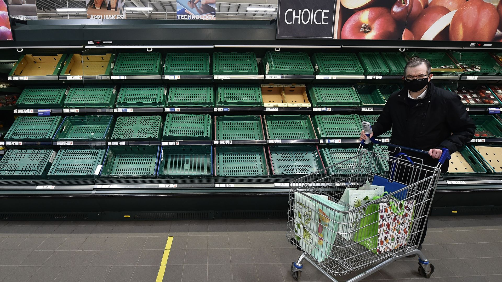 A supermarket shopper walks past rows of empty shelves in Tescos on January 14, 2021 in Belfast, Northern Ireland. Shortages and higher prices could soon be seen on the mainland - Credit: Photo by Charles McQuillan/Getty Images