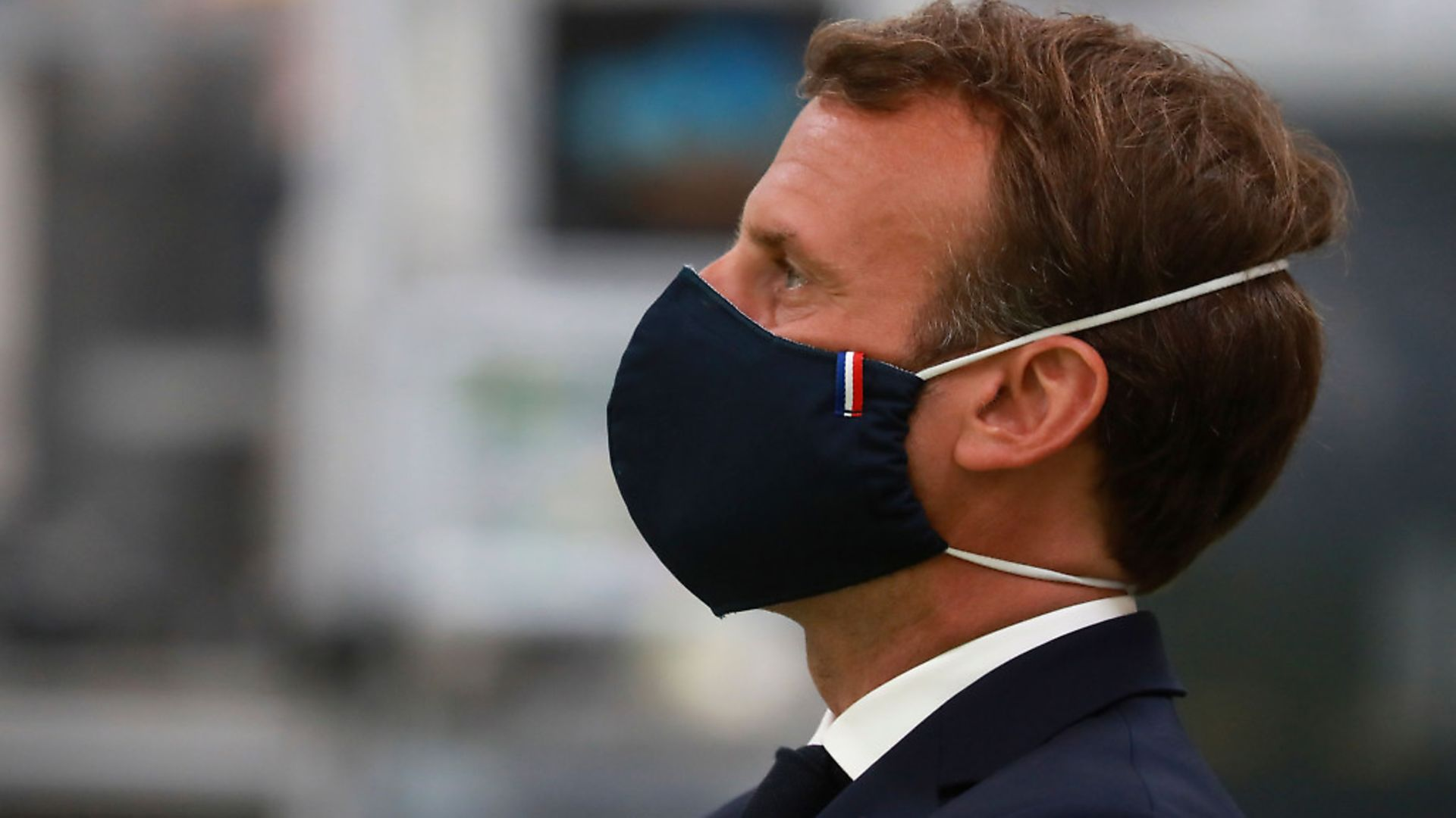 French President Emmanuel Macron, wearing a protective face mask, looks on as he visits a factory of manufacturer Valeo in Etaples, near Le Touquet, northern France. Photo: Getty Images - Credit: POOL/AFP via Getty Images