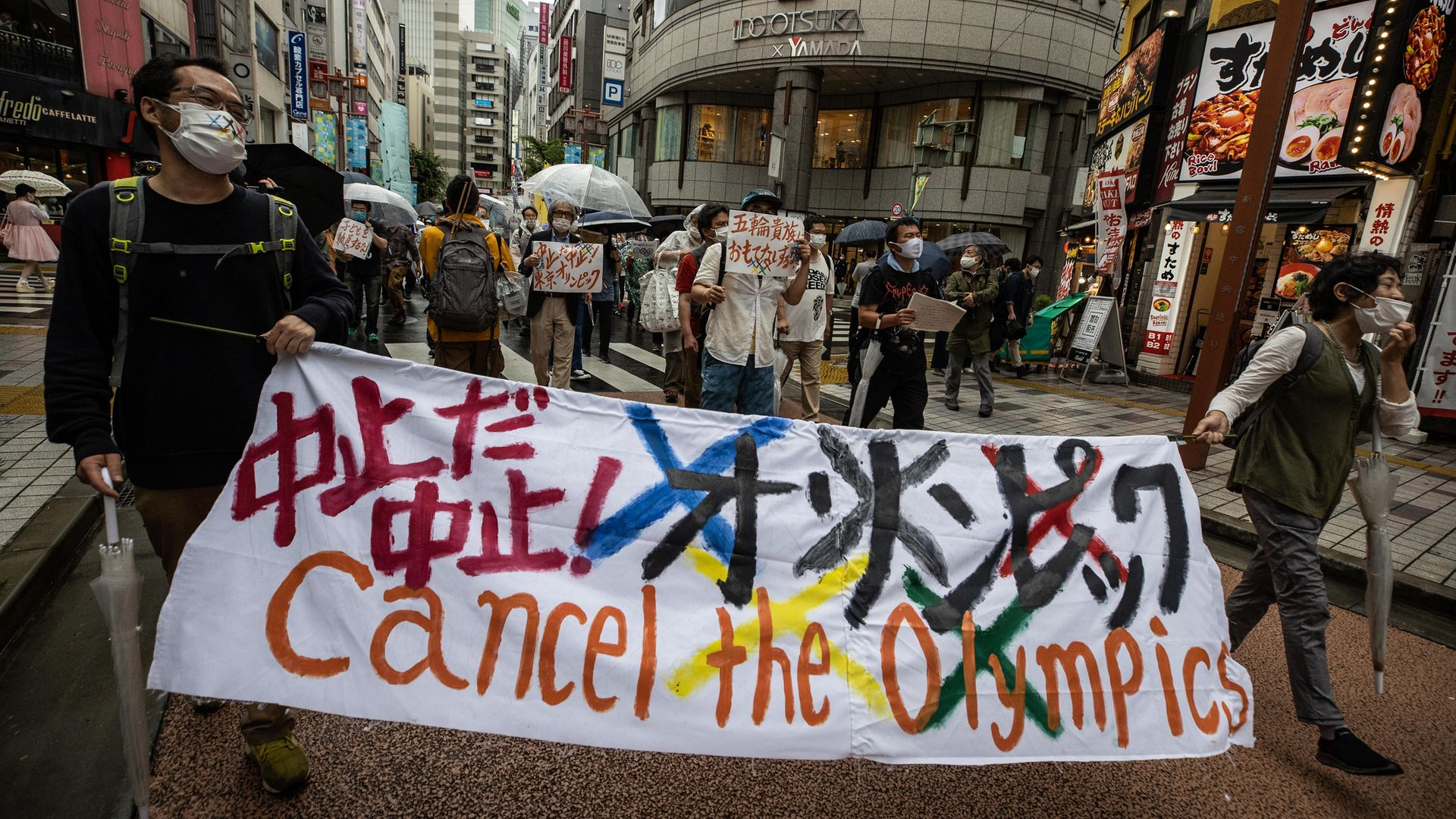 Protesters march through Shinjuku during a rally against the Tokyo 2020 Olympic Games on June 19, 2021 - Credit: Photo by Takashi Aoyama/Getty Images