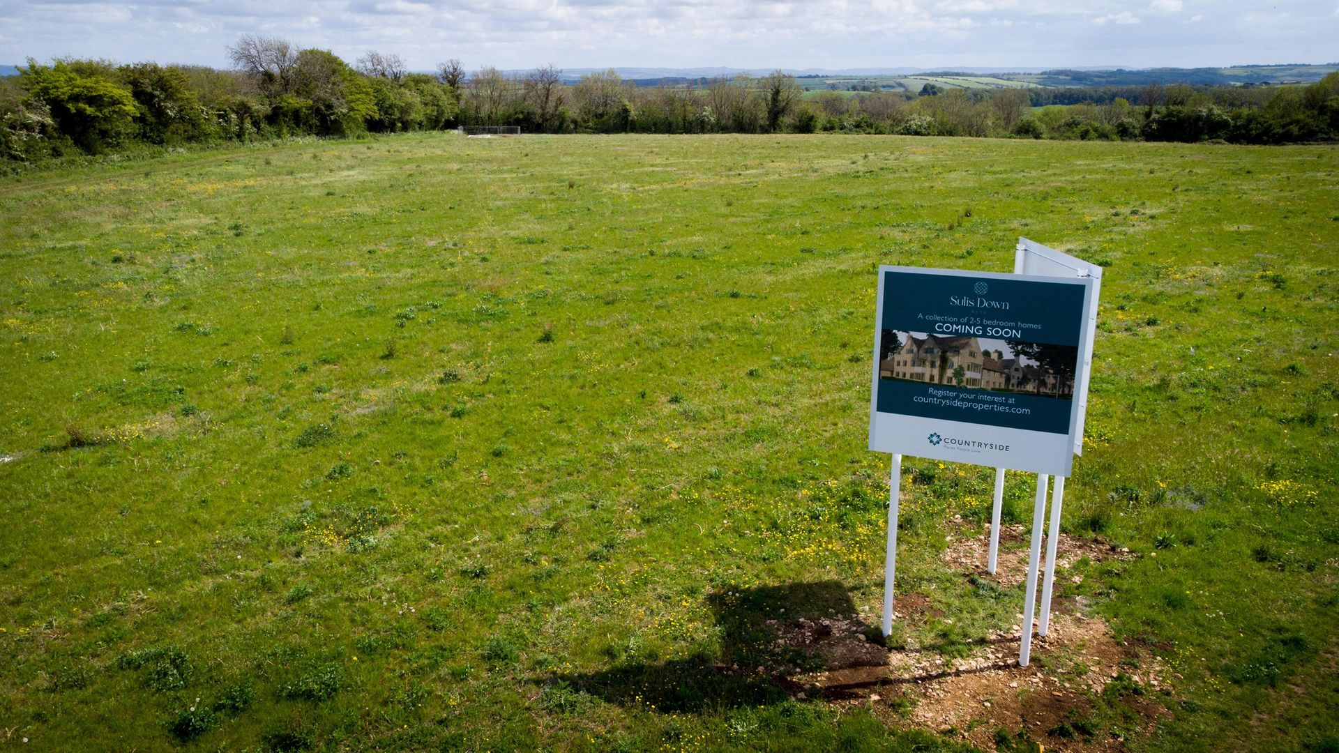 SIGN OF THINGS TO COME: A property developer's board advertises new houses that are planned to be built on green belt land on the edge of Bath - Credit: Matt Cardy