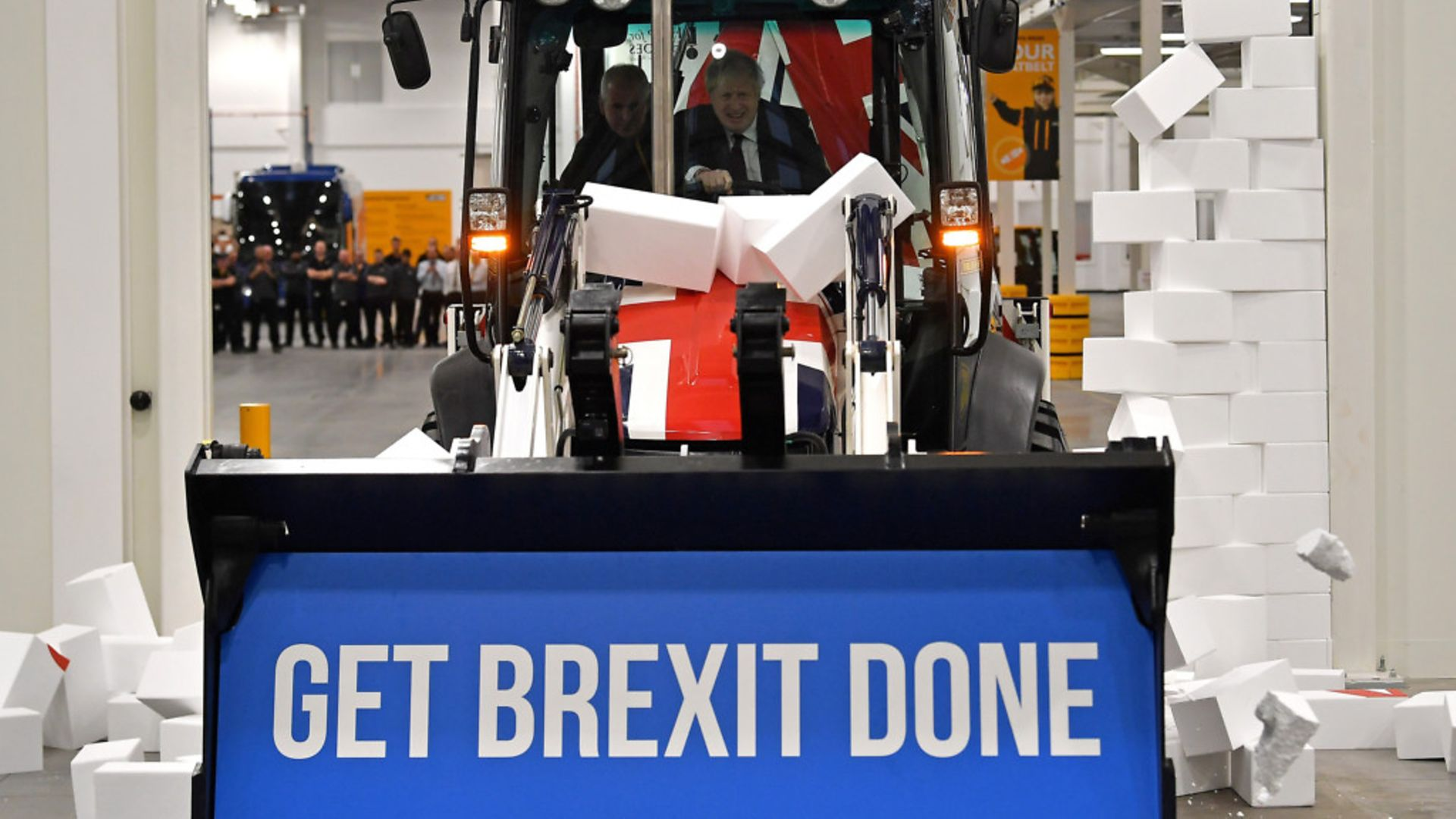 """Boris Johnson drives a union flag-themed JCB, with the words """"Get Brexit Done"""" inside the digger bucket, through a fake wall - Credit: Getty Images"""