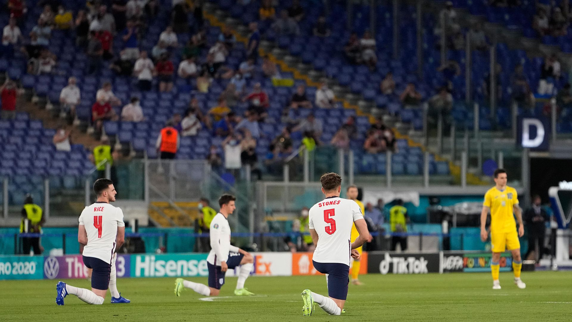 Declan Rice and John Stones of England take a knee while Ukraine players remain standing before their quarter-final - Credit: Photo by Alessandra Tarantino - Pool/Getty Images