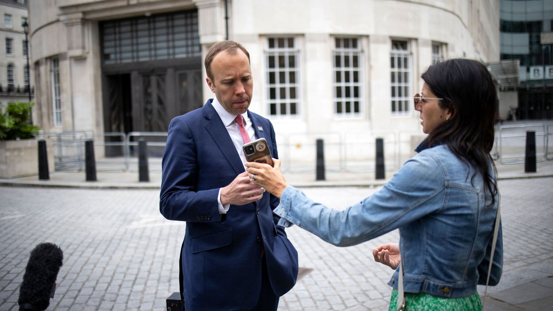 WhatsUp? Matt Hancock looks at the phone of his aide Gina Coladangelo as they leave the BBC in central London in June. Weeks later, news of the pair's affair - and Hancock's use of Gmail and WhatsApp for government business - emerged - Credit: AFP via Getty Images