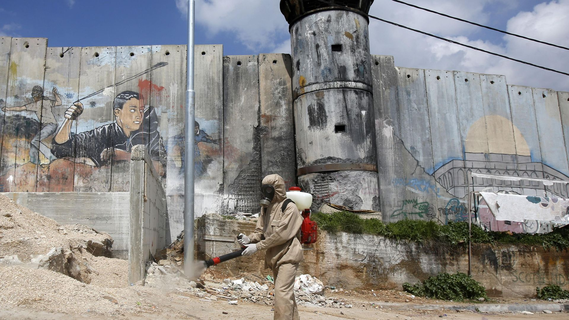 Bedlam or Bethlehem? In this apocalyptic image, a Palestinian sanitary department worker sprays disinfectant along a security border in Bethlehem, during the pandemic - Credit: AFP via Getty Images