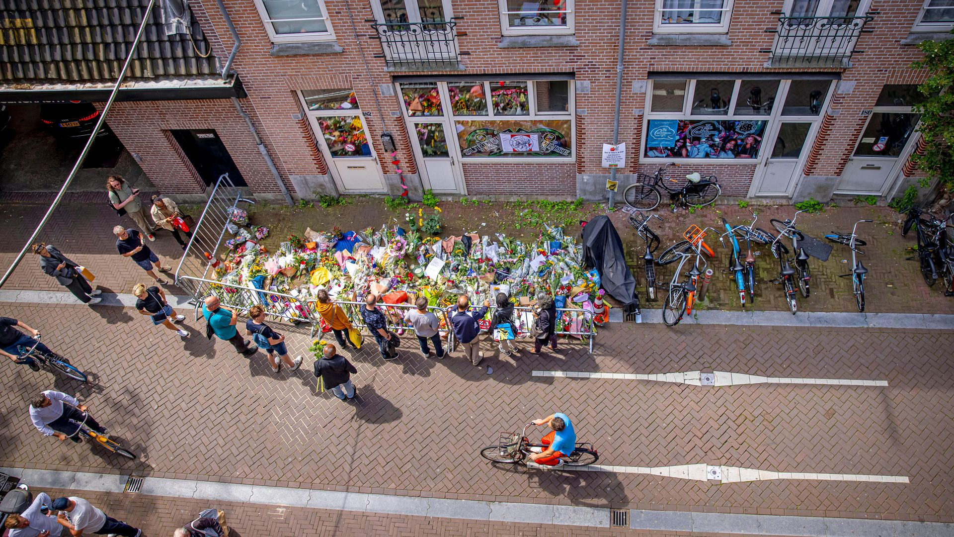 People lay flowers at the place in Amsterdam's Lange Leidsedwarsstraat, where crime reporter Peter R De Vries was shot - Credit: Getty Images