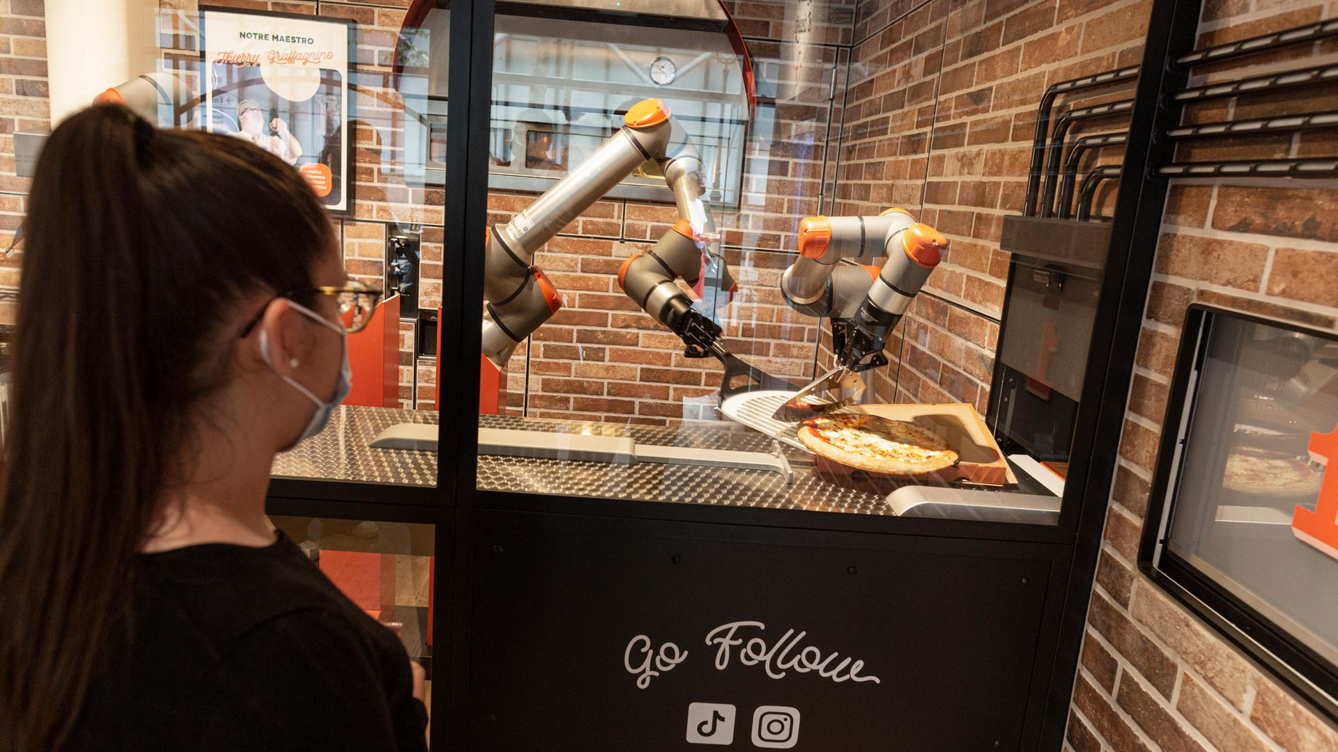 A woman watches as her pizza is prepared at Pazzi, Paris' first robotic pizzeria - Credit: Photo by Sam Tarling/Getty Images