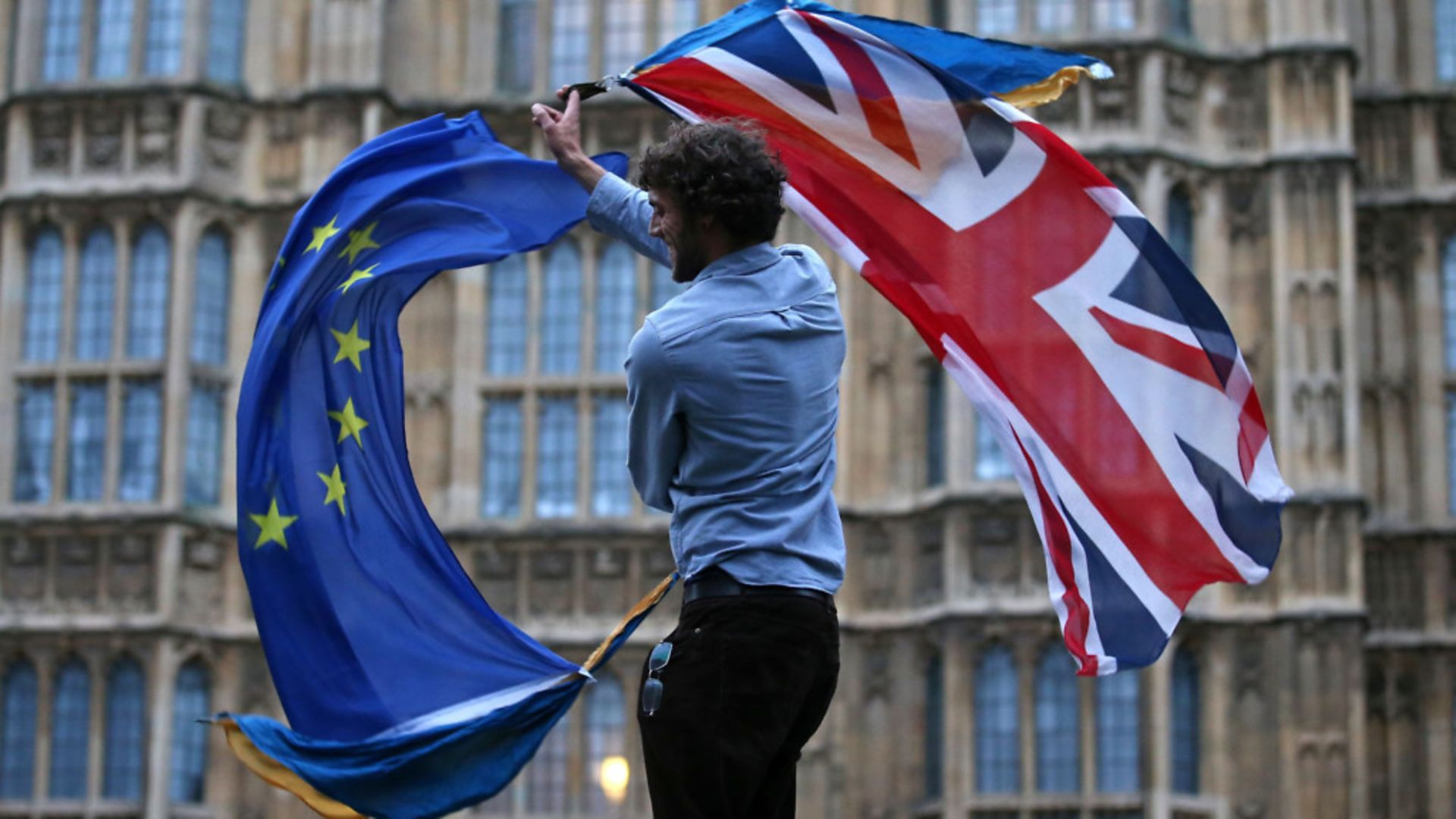 A man waves both a Union flag and a European flag together on College Green outside the Houses of Parliament - Credit: AFP via Getty Images