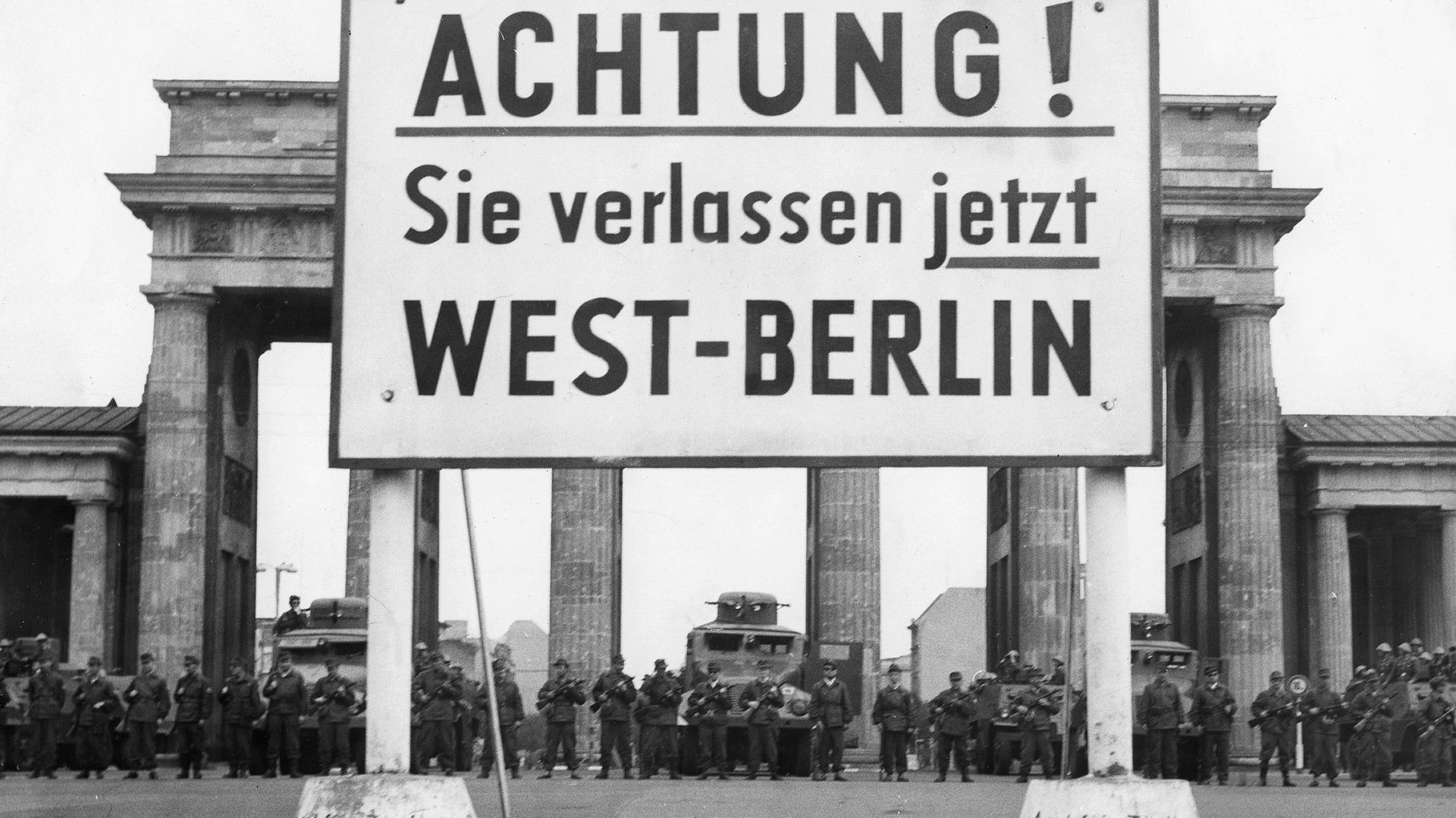 Guards at stand at the Brandenburg Gate, as the Berlin Wall goes up behind them, in August 1961 - Credit: ullstein bild via Getty Images