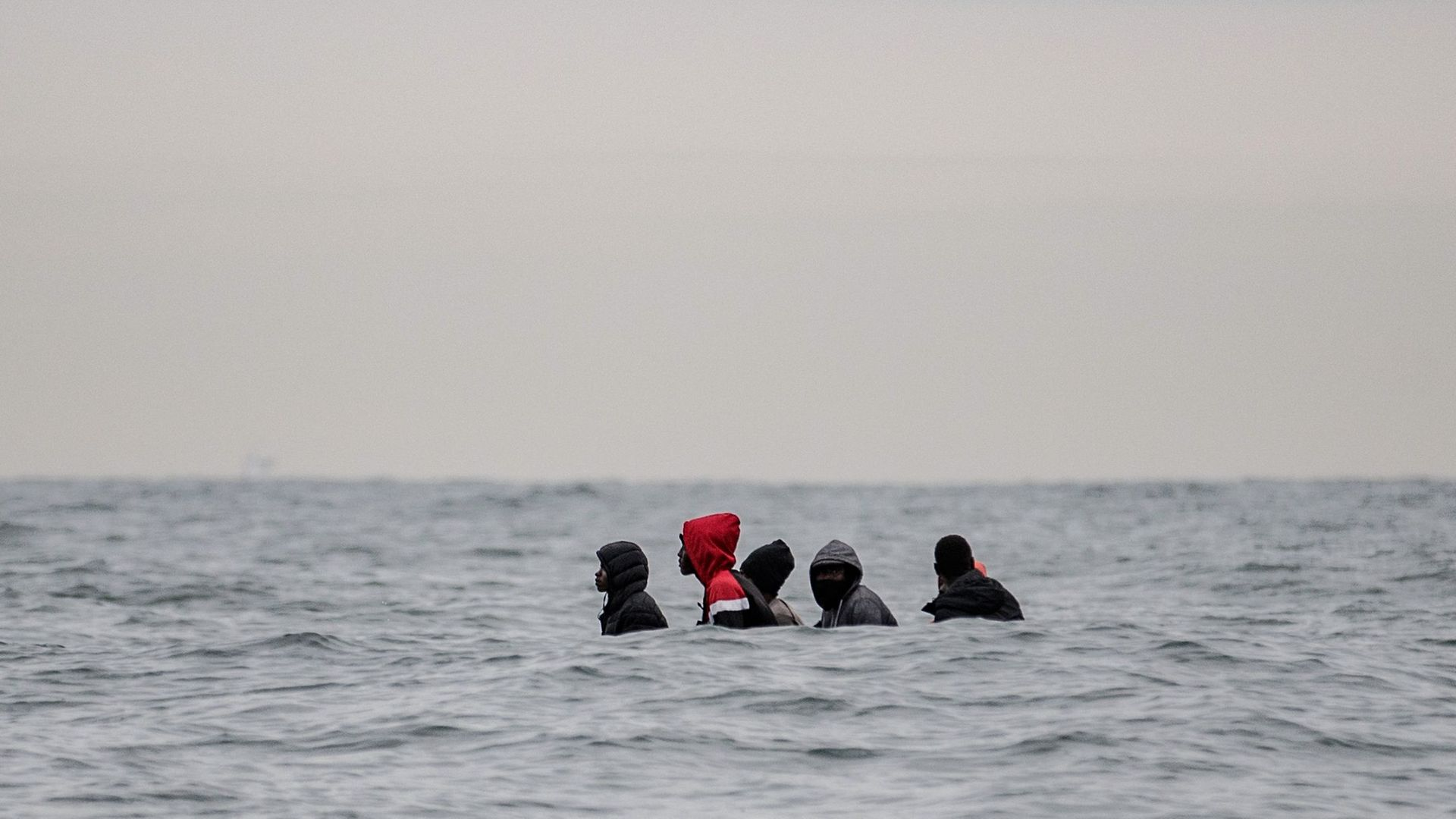 Migrants on a small boat in the waters off Cap Blanc-Nez heading to Britain - Credit: AFP via Getty Images