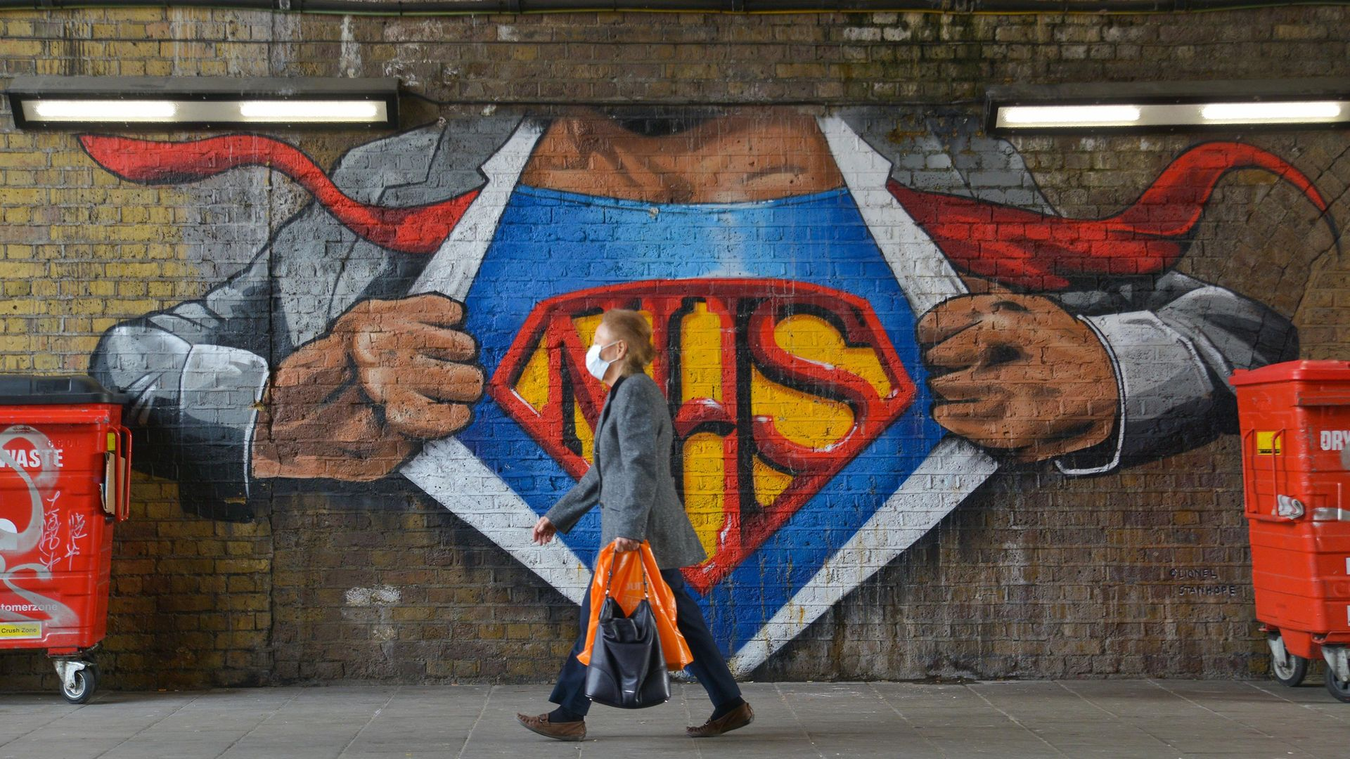 A woman wearing a face mask as a precaution against the spread of Covid-19 walks past a graffiti tribute to the NHS in Waterloo, London - Credit: Photo by Thomas Krych/SOPA Images/LightRocket via Getty Images