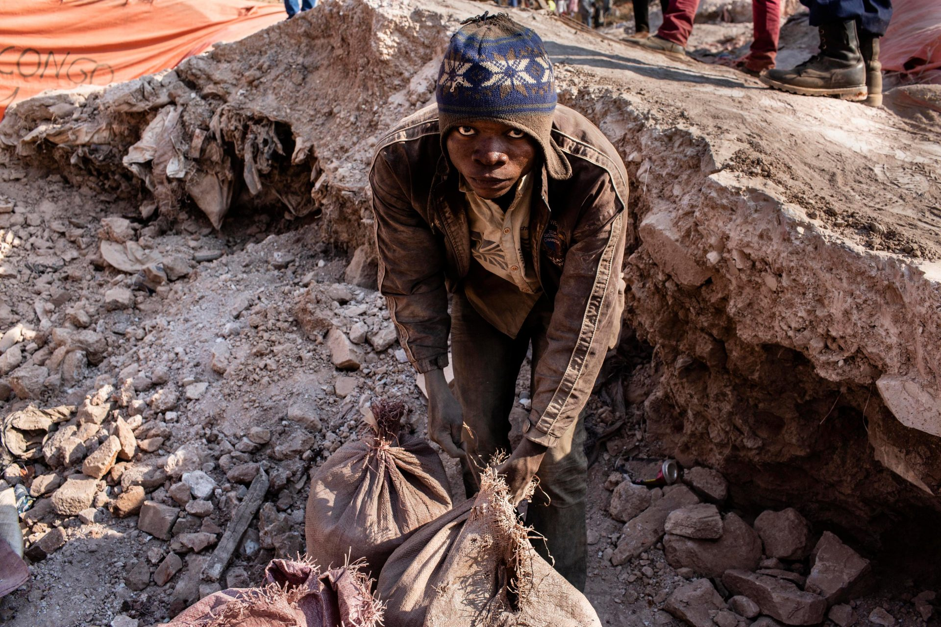 A young miner in Kolwezi, in the Democratic Republic of Congo, fastens bags of cobalt, a vital component in many modern electrical devices. Photo: Sebastian Meyer/ Corbis via Getty Images