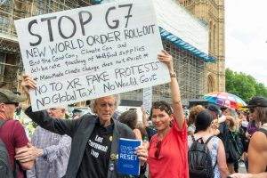 Piers Corbyn and a rallygoer hold a placard outside the Houses of Parliament. Photo: Dave Rushen/SOPA Images/LightRocket via Getty Images.