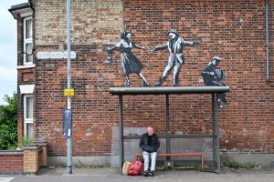 A man and his shopping at a bus stop in Great Yarmouth, below Banksy's graffiti artwork of a couple dancing to an accordion player. Photo: Justin Tallis/AFP via Getty Images.