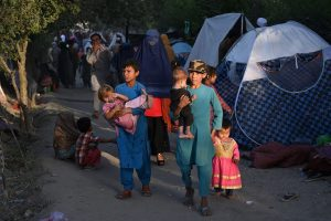 Displaced Afghan families, who fled from Kunduz, Takhar and Baghlan province as the Taliban approached, walk past their temporary tents at Sara-e-Shamali in Kabul on August 11. Photo: Wakil Kohsar/AFP via Getty Images.