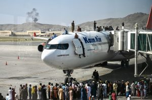 Afghan people climb atop a plane as they wait at the Kabul airport. (Photo by Wakil Kohsar / AFP)