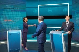Chancellor candidate Annalena Baerbock of the Greens fistbumps the SPD's Olaf Scholz after their first TV debate with Armin Laschet of the CDU. Photo: Michael Kappeler/Pool/Getty Images.