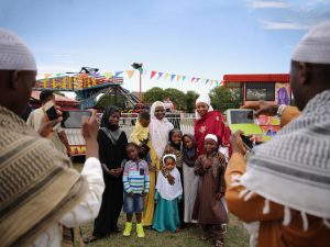 A family have their photograph taken after morning prayers during an Eid celebration in London's Burgess Park. The Muslim holiday Eid marks the end of 30 days of dawn-to-sunset fasting during the holy month of Ramadan.   Photo: Dan Kitwood/Getty Images.