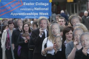 Students wearing Sir Alan Sugar masks at the launch of a campaign to boost the take-up of apprenticeships in the UK. Yet despite a series of reforms, the scheme has proved costly and inefficient. Photo: Matt Cardy/Getty Images.