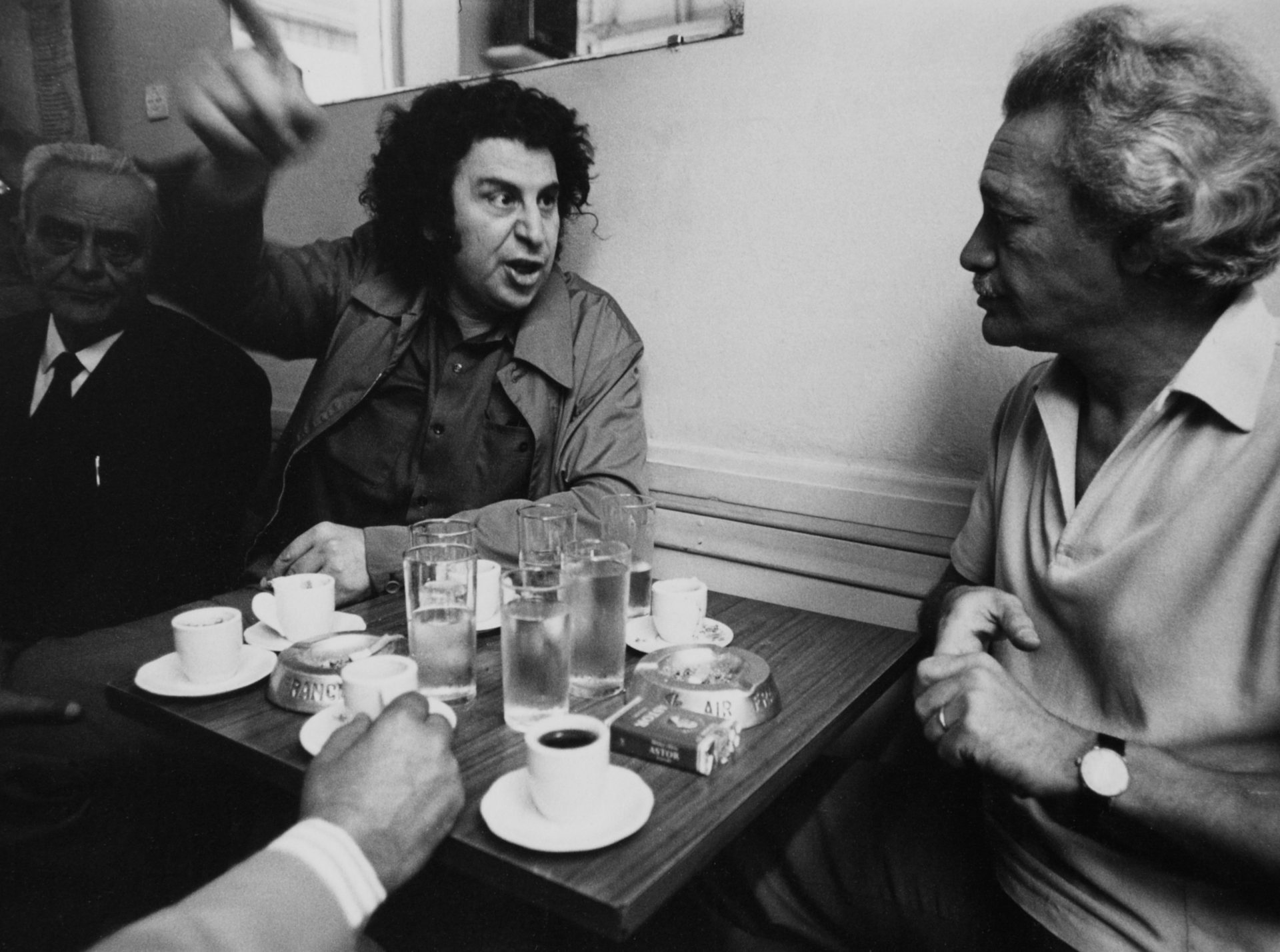 Mikis Theodorakis is wrapped up in a political discussion in an Athens pub after returning from exile. Credit: Wolfgang Kunz/ullstein bild via Getty Images