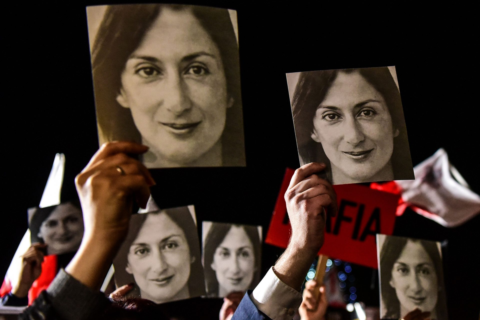 """People holding placards reading """"Mafia Government"""" and photos of killed journalist Daphne Caruana Galizia outside the office of the prime minister in Valletta, Malta. (Photo by STRINGER/AFP via Getty Images)"""