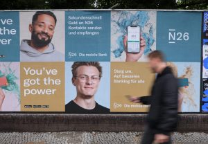 A man with a smartphone walks past a billboard advertising German internet bank N26 in Berlin, Germany (Photo by Sean Gallup/Getty Images)