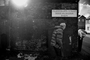 A man walks past a dual Irish-English language street sign in Belfast. Photo: Charles McQuillan/Getty Images.