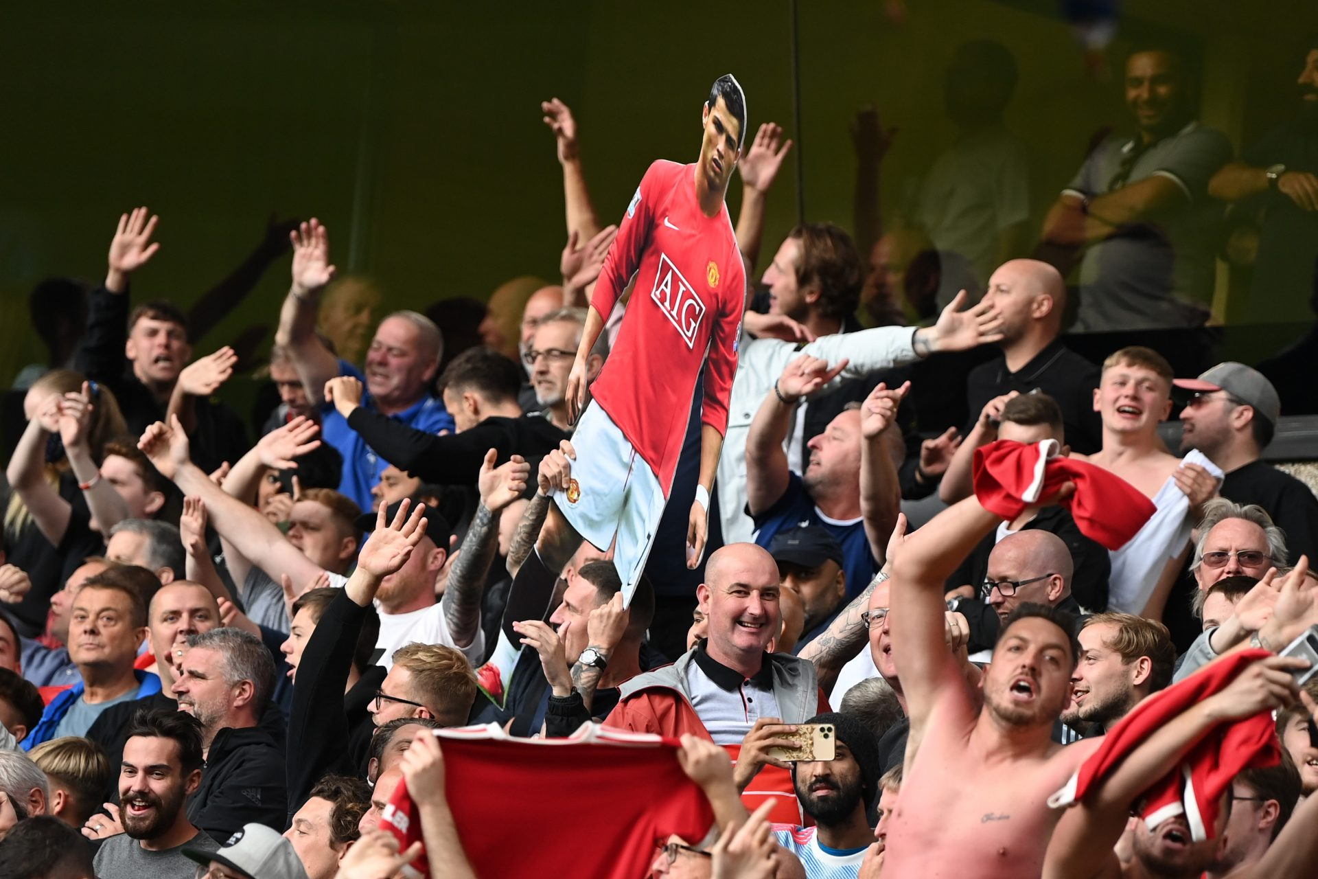 Manchester United fans hold up a cardboard cutout of Cristiano Ronaldo during their win at Wolves on August 29. Credit: Shaun Botterill/Allsport/ Getty; Kevin C Cox/Getty Images