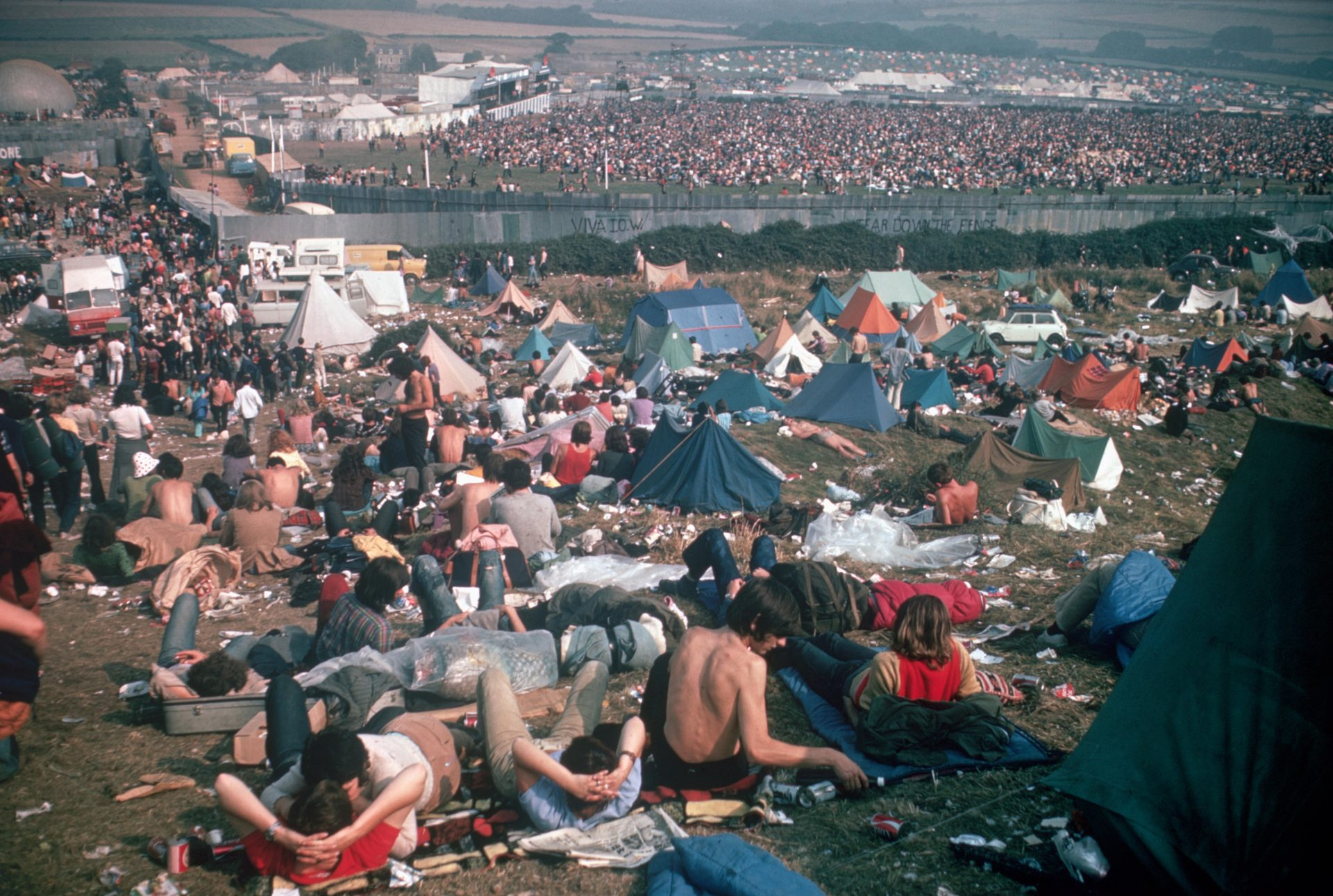 Festivalgoers on a hillside look down on the jammed stage area behind fences during the 1970 Isle of Wight Festival. Credit: Bettmann Archive