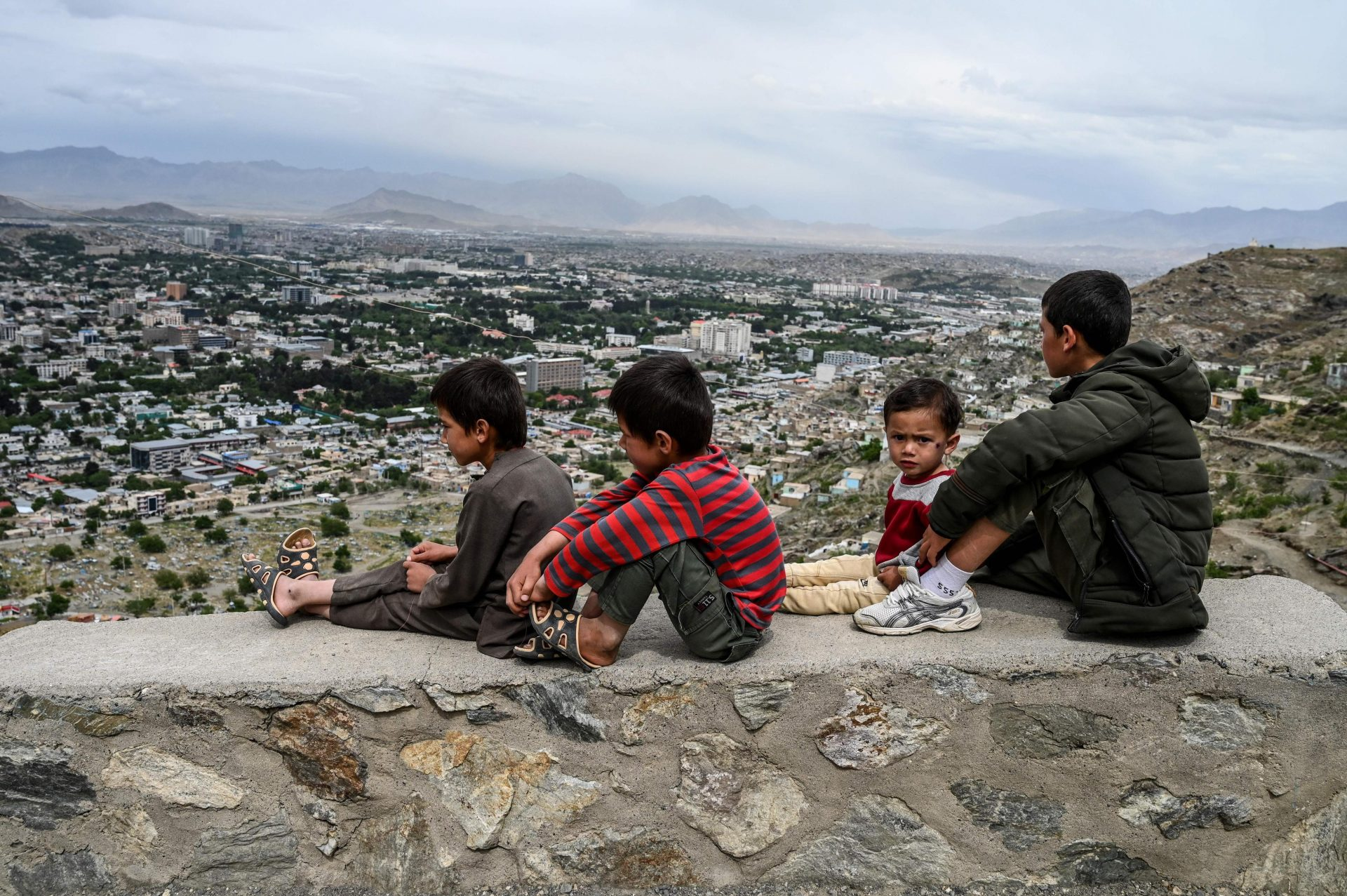 Children sit on a wall overlooking the city of Kabul,2020. Credit: WAKIL KOHSAR/AFP via Getty.