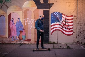 A skateboarder passes graffiti on a mural of a US flag in Minneapolis, Minnesota. Photo: Kerem Yucel/ AFP via Getty Images.