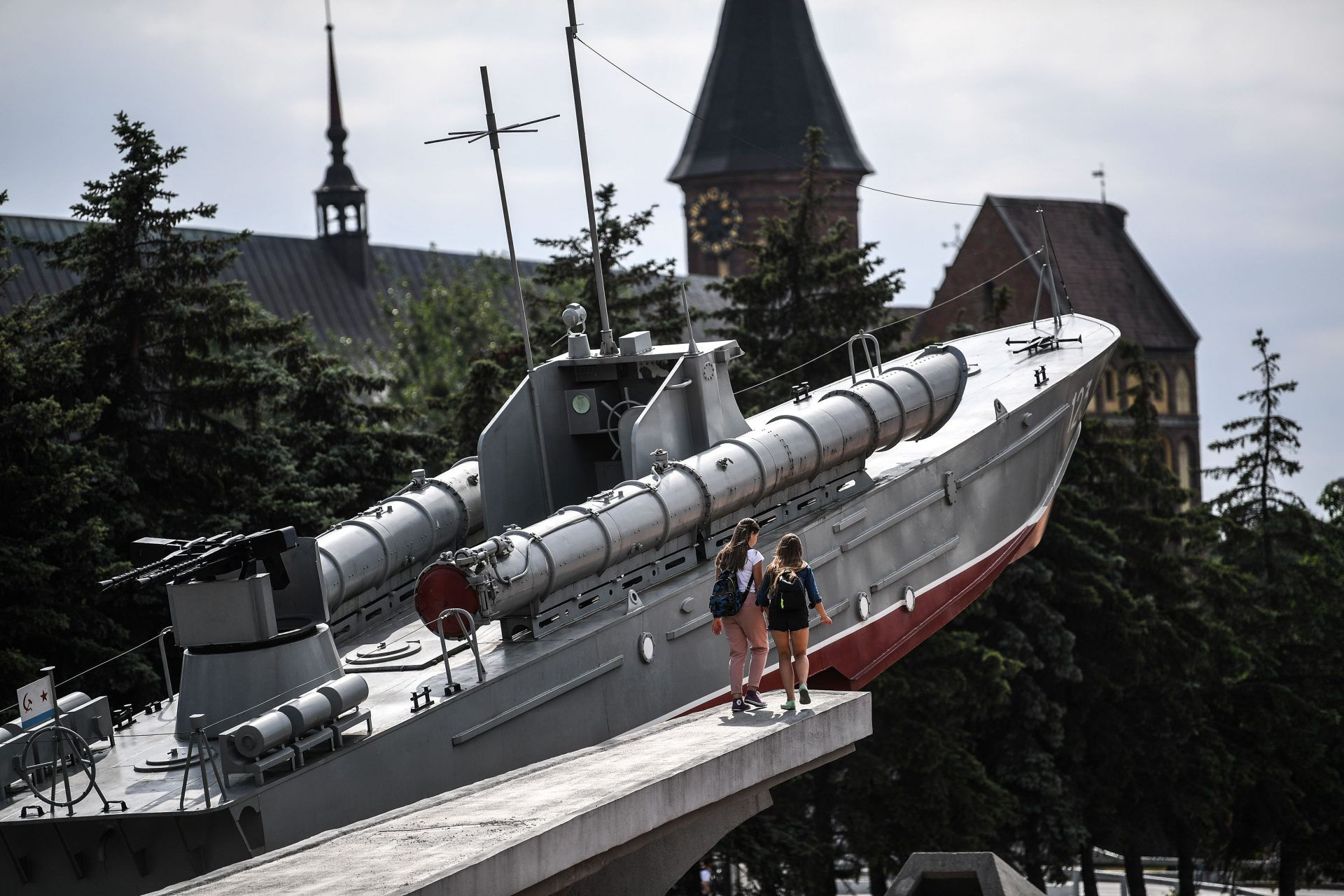 Children walk next to a memorial featuring a Soviet torpedo boat from the Second World War in Kaliningrad. Photo: Ozan Kose/AFP/Getty Images