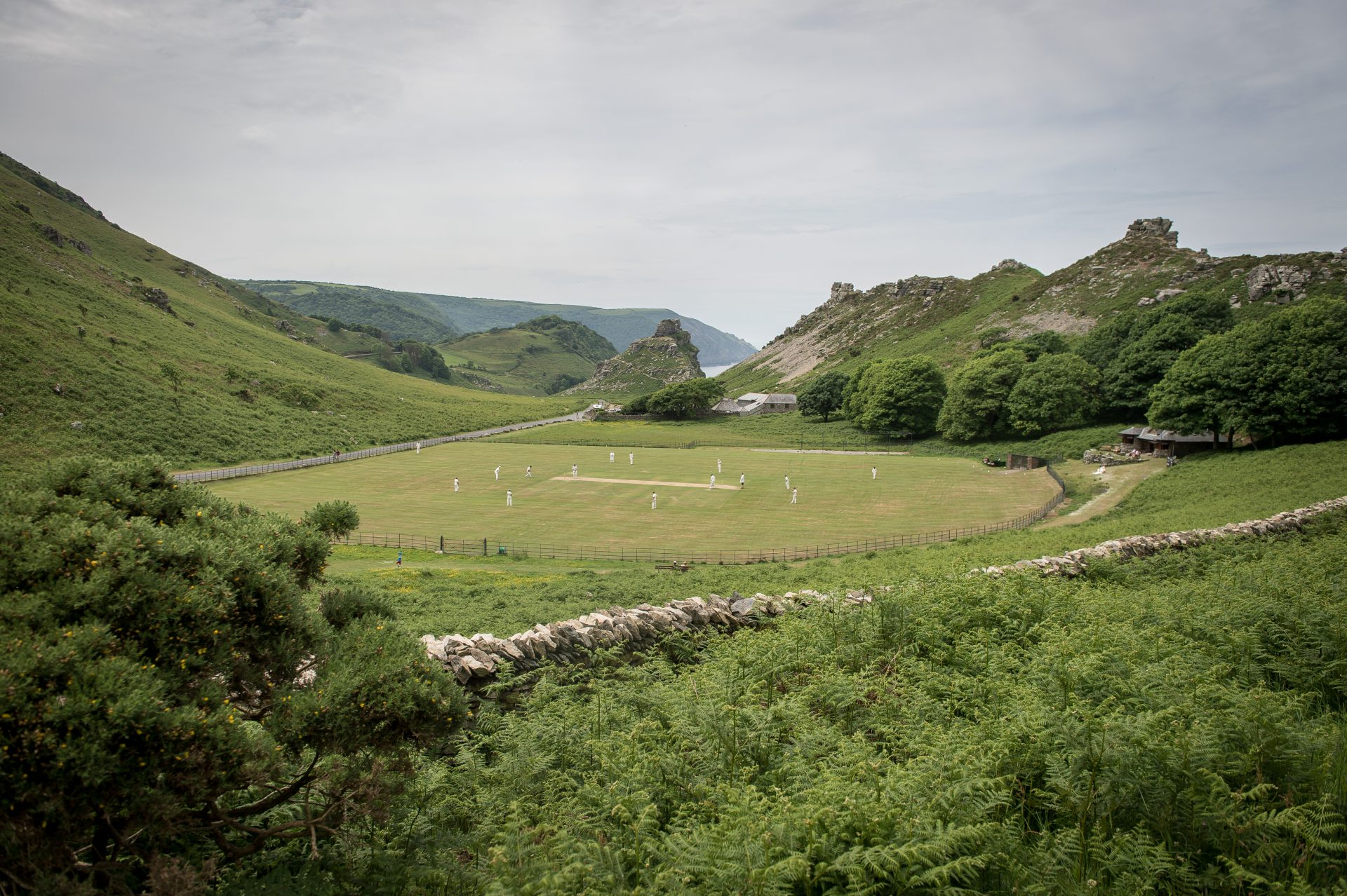Match play on the pitch during an annual friendly match between Cravens Cavaliers and Lynton & Lynmouth Cricket Club at their ground based inside the Valley of Rocks, North Devon. Credit:  Ben Birchall/PA Archive/PA Images